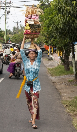 festiva: BALI, INDONESIA - JUL 8TH  A woman carries a basket of fruit to the temple on July 8th 2011 during the Galungan festival which is held in the 11th week of the 210-day Pawukon calendar  Editorial