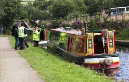 escorting: DIGGLE, ENGLAND - Aug 19TH  Waterway officials check boats before escorting them through Standedge tunnel on August 19th 2011  The tunnel is the longest and highest canal tunnel in the U K
