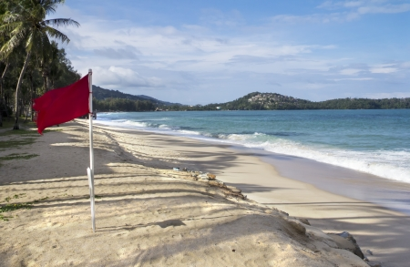 Red flag flying on Bang Tao beach, Phuket, Thailand indicating that it is dangerous to swim Stock Photo - 23056302