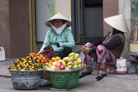 non la: Street vendors selling fruit in Ho Chi Minh