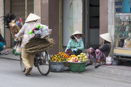 non la: HO CHI MINH CITY, VIETNAM-NOV 3RD: Street vendors in Ho Chi Minh City on November 3rd 2013. Street vendors are a common site in Ho Chi Minh