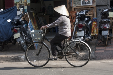 non la: HO CHI MINH CITY, VIETNAM-NOV 3RD: A woman cycles down a street in Ho Chi Minh City on November 3rd 2013. Cyclists are becoming less common as more and more people can afford motorcycles and scooters.