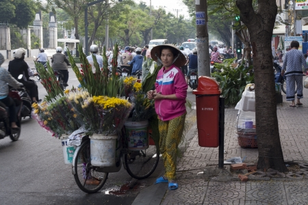 non la: HO CHI MINH CITY,VIETNAM-NOV 5TH: A flower seller on November 5th 2013. Many street vendors can be found selling their wares in Ho Chi Minh. Editorial