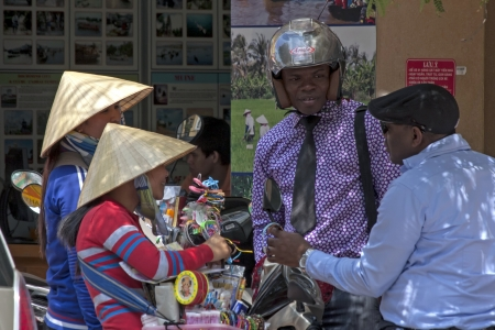 non la: HO CHI MINH CITY,VIETNAM-NOV 3RD: Tourists negotiate with street vendors on  November 3rd 2013. Vietnam received 7 million tourists in 2012.