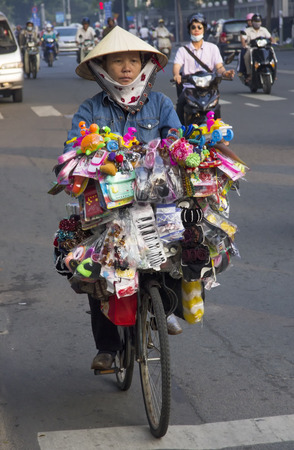 non la: Ho Chi Minh City, Vietnam-October 29th 2013  A trinket vendor riding her bicycle through the Ho Chi Minh traffic  Bicycles have been replaced by motorcycles as the main form of transport in Vietnam