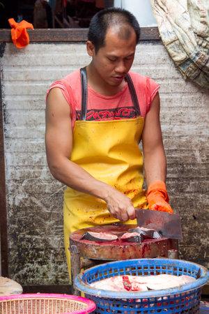 fishmonger: Bangkok, Thailand-June 24th 2013: A fishmonger preparing fish for sale at Khlong Toei market. The market is the largest wet market in Bangkok. Editorial