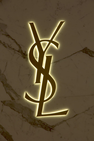 laurent: Bangkok, Thailand-May 17th 2014. The Yves Saint Laurent logo on a store in the Embassy Mall. The brand was founded in 1961by Pierre Berge and Yves Saint Laurent who died in 2008.