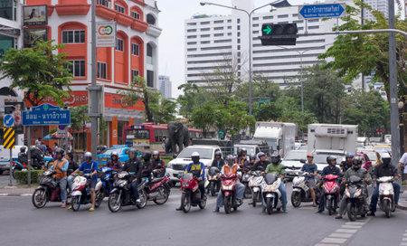 notorious: Bangkok, Thailand-April 30th 2014: Cars and motorbikes waiting at traffic lights in Bangkok Bangkok is notorious for its traffic congestion.
