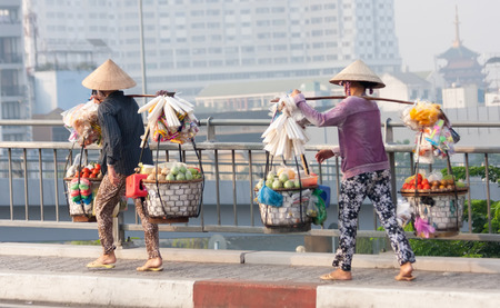 laden: Ho Chi Minh City, Vietnam-Nov 1st 2013: 2 heavily laden street vendors crossing the bridge over the river on the way back from the market. Vendors stock up early in the morning before selling their wares on the street. Editorial