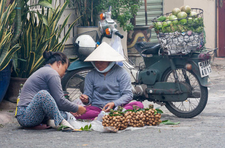 non la: Ho Chi Minh City, Vietnam-Nov 1st 2013: 2 women fruit vendors sorting longan fruit. Street vendors can be found all over the city. Editorial