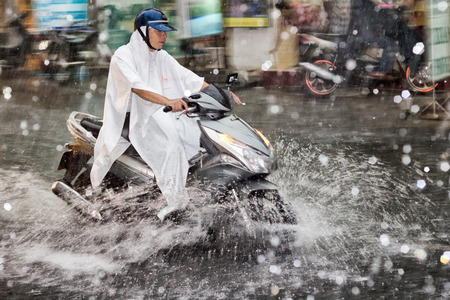 torrential: Ho Chi Minh City, Vietnam-Nov 1st 2013: Scooter driving through the floods and torrential rain. The city is prone to heavy bursts of rain which often cause localised flooding. Editorial