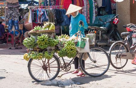 non la: Ho Chi Minh City, Vietnam-Nov 2nd 2013: Mobile banana vendor on a bike. Many vendors still use bicycles to peddle goods. Editorial