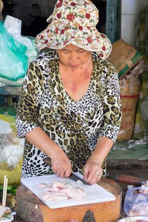 visboer: Ho Chi Minh City, Vietnam-2 november 2013: Vrouw visboer snijden vis op Cholon markt. Cholon is het Chinatown van de stad.