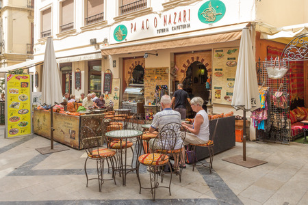 al fresco: Malaga, Spain-August 31st 2015: People eating in an outdoor restaurant. Most restaurants in Malaga have seating outside.