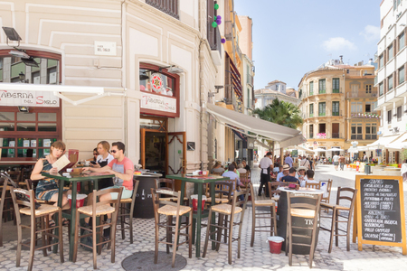 Malaga, Spain-August 26th 2015: People eating outside a restaurant. Al fresco dining is very popular both at lunchtimes and evenings.