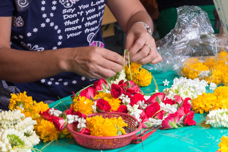 bangkok, Thailand-June 18th 2013: Making garlands at Pak Khlong Talat flower market. Thousand of garlands are made every day.