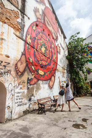 Phuket Town, Thailand - 6th August 2018: Chinese tourists posing in front of wall mural, Millions of tourists vist from China each year.