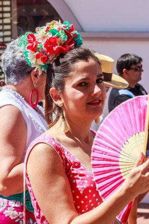 Arroyo de la Miel, Spain - 17th June 2018: Girl with fan wearing a fascinator at a local fiesta. Spain is famous for its fiestas.