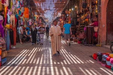 September 15th 2010 - Marrakech, Morocco: Beggar walking through souk. The lattice keeps the shoppers out of the sun. Editorial
