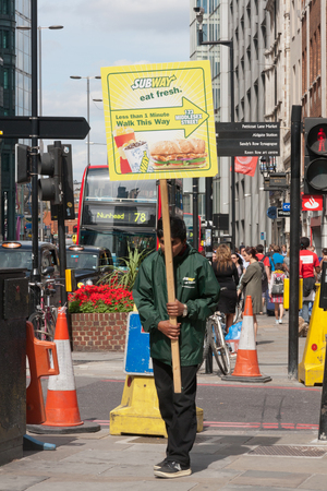 London, England - August 22nd 2011: Man carrying boards advertising Subway sandwich shop, Bishopsgate. Subway is an American chain.