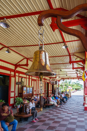 Hua Hin, Thailand - July 13th 2010: Station bell and passengers waiting for the train to Bangkok. The station is on the mainline between Bangkok and the south of Thailand