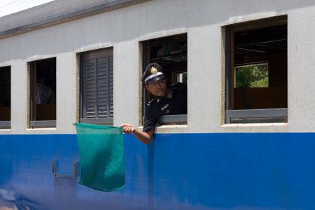 Train guard holding up a green flag to stop a train coming into Hua Hin railway station, Prachuap Khiri Khan, Thailand