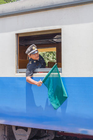 Hua Hin, Thailand - July 13th 2010: Train guard signalling with green flag. The station is on the mainline between Bangkok and the south of Thailand Editorial