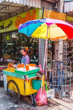 Bangkok, Thailand - April 21st 2011. Orange juice vendor under a colourful umbrella. Fruit juices are a popular drinl.