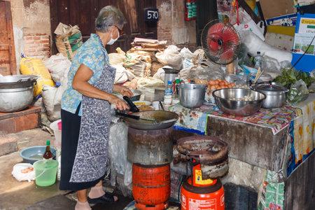 Bangkok, Thailand - March 23rd 2015: Woman cooking, steet kitchen, Chinatown, Bangkok, Thailand 報道画像