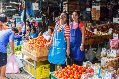Bangkok, Thailand - 11th March 2017: Girls laughing on vegetable stall. Pak Khlong Talat is citys biggest wet market Redactioneel