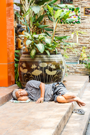 Bangkok, Thailand - 4th August 2017: Old man asleep on some steps. Vagrancy is an ever increasing problem.