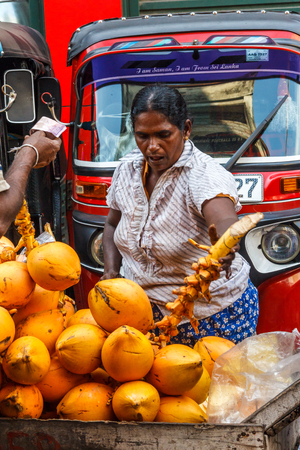 Colombo. Sri Lanka - December 21st 2016: Woman buying coconuts in the Pettah district. This is the main commercial area.