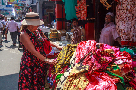 Colombo. Sri Lanka - December 21st 2016: Woman tourist shopping for material in the Pettah District. This is the main commercial area.