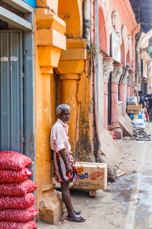 Colombo. Sri Lanka - December 21st 2016. Man leaning against a  wall in the  Pettah district. This is the main commercial area.