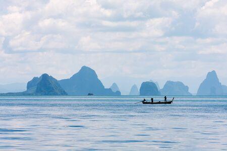 Two men in a boat fishing in Phang Nga Bay, Phuket, Thailand