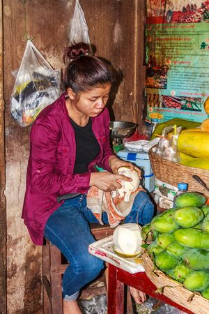 Siem Reap, Cambodia - 15th January 2018 Woman vendor peeling a pomelo  in the old market, The market is open every day for local produce.