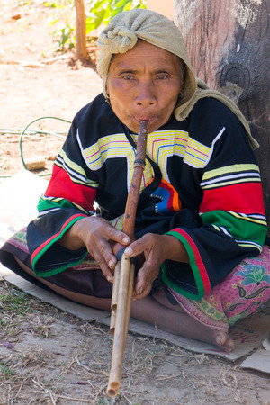 Chiang Rai, Thailand - December 10th 2014: Lahu hilltribe woman playing a wind instrument. There are many hill tribe people in the area.
