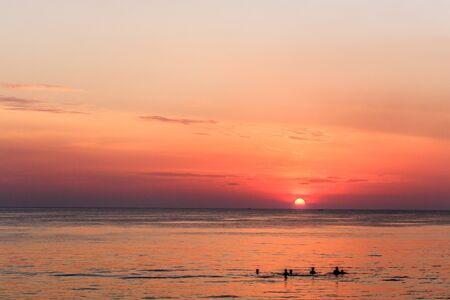 People swimming in the sea at sunset. Bang Tao beach, Phuket, Thailand