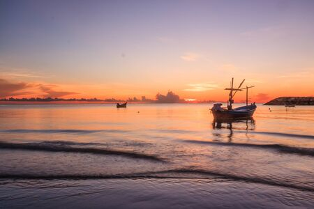 Boats on the water at dawn in Cha Am, Thailand Stock Photo