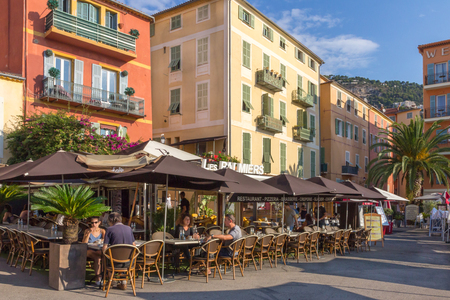 Villefranche sur Mer, France - September 9th 2015: People eating and drinking in a cafe restaurant. The cafe is located on the harbourside. Editorial