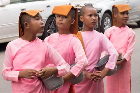 Yangon, Myanmar - May 5th 2014: Novice nuns line up ready to collect alms. Monks and nuns are a common sight in the city. Banque d'images - 128406380