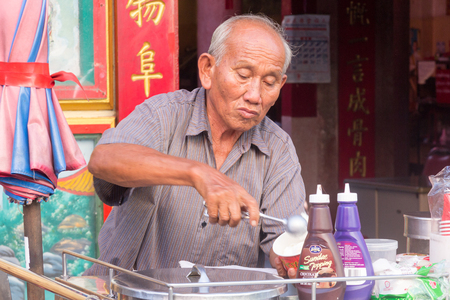 Chiang Mai, Thailand - November 22nd 2015: Man selling and serving ice cream outiside a Chinese temple. Coconut ice cream is a particular favourite,