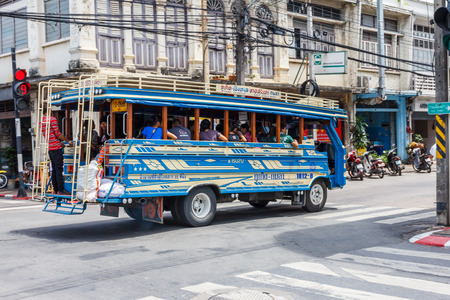 Phuket, Thailand - July 23rd 2014: A local bus drives through the junction of Thalang Road and Yaowarat Road. Buses travel to all parts of the the island from the old town