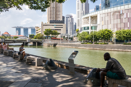 Singapore - July 8th 2019: People relaxing by the SIngapore River. The river runs through the city centre.