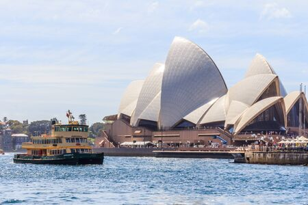 Sydney, Australia - March 23rd 2013: The Manly ferry passing the Opera House. The ferry operates on a regular basis every day.