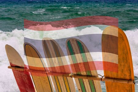 Surfboards against a rough sea background with Thai flag superimposed. Digital composite image.