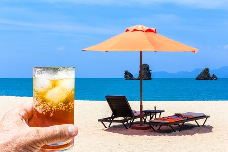 Hand holding glass of rum and coke with ice against sunloungers and a parasol on an empty Langkawi beach, Malaysia