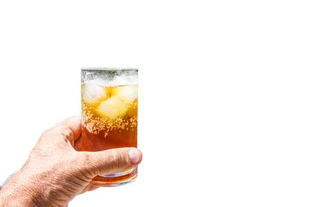 Hand holding a rum and coke cocktail in glass with ice Standard-Bild