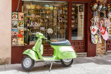 Toledo, Spain - 6th June 2018: : Lime green scooter parked outside souvenir shop. Scooters are ideal for travelling around the narrow streets.