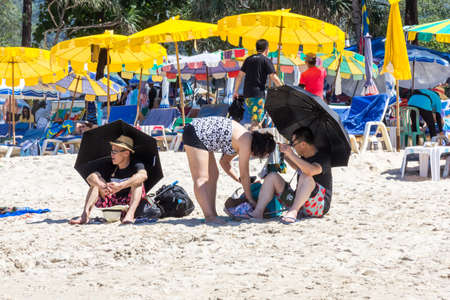 Phuket, Thailand - 11th December 2017: Asian tourists with black umbrellas on Patong beach. Many tourists come from all over the world. Editorial